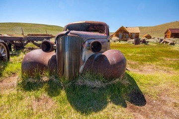 Vintage rusty car in Bodie with town in background - California