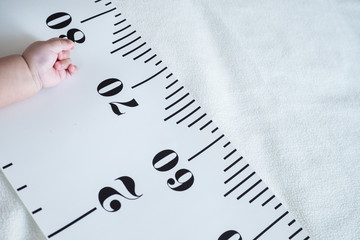 Baby hand and measuring tape: concept of baby growth, height, development