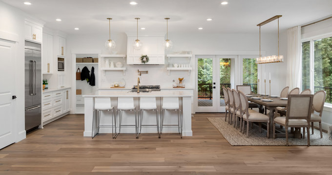 Beautiful kitchen and dining room panorama in new luxury home, with pendant lights, dining room table and chairs, kitchen island, and counters