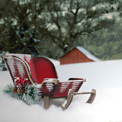 A red Christmas sleigh in the snow.