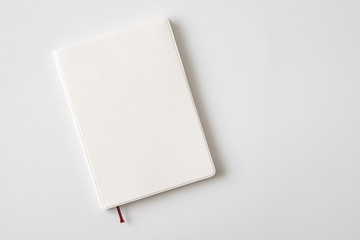 Top view of closed blank white leather cover notebook on white desk background with copy space