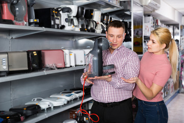 Couple buying coffee machine for kitchen in home appliances shop
