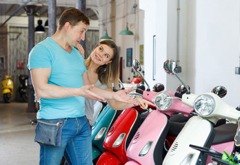 Couple is shopping and choosing new motobike