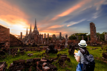 Tourist women with Carrying a backpack Viewing poster, About the temple in Ayutthaya At  Phra Si Sanphet 3 Pagoda Temple.Concept travel in relax..