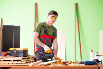 Young man carpenter working in workshop