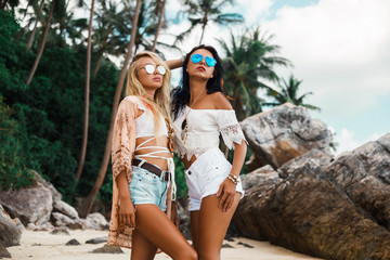Two cute beautiful girls in Boho style dressed shirts shorts light cape bracelets necklaces, in hair decorative feathers colored standing in the sensual pose against sea and rocks, feeling of freedom