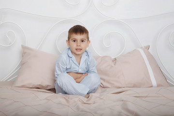 Little boy in blue pajamas tumbles in bed with bed linen and pillows.