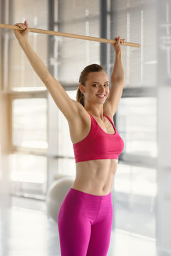Smiling fit slim woman training with fitness stick