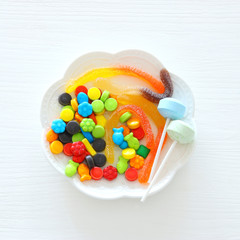 Halloween holiday minimal top view image of trick or treat sweets over wooden background.