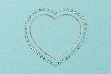 Heart shaped frame of diamonds and yellow gold on tiffany blue background. 3D rendering