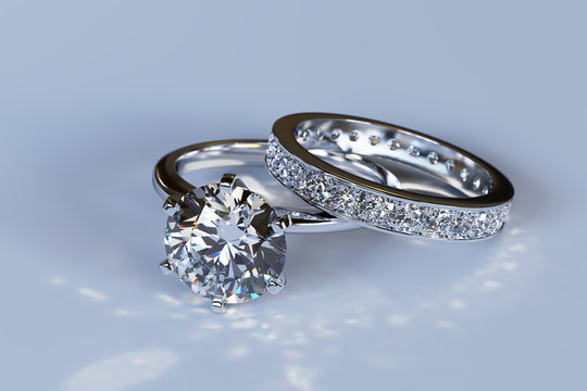 Wedding set, solitaire diamond engagement ring, channel setting eternity wedding bad on blue glossy background. 3D rendering