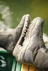 Male and female tactical army boots of travellers meeting side by side on boat with water in background