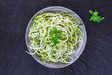 Courgette spaghetti - shredded zucchini on a plate - top view