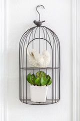 bird statue and small artificial plant in cage hanging on white wall.