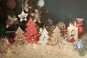 Four decorative wooden Christmas trees with carved letters xmas and christmas ornaments. Christmas family traditions.