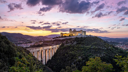 Fototapete - Spoleto on sunset. Ponte delle torri medieval bridge and Rocca Albornoziana hilltop fortress, Province of Perugia, Italy