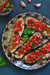 Spicy baked eggplant grilled with tomatoes and peppers.