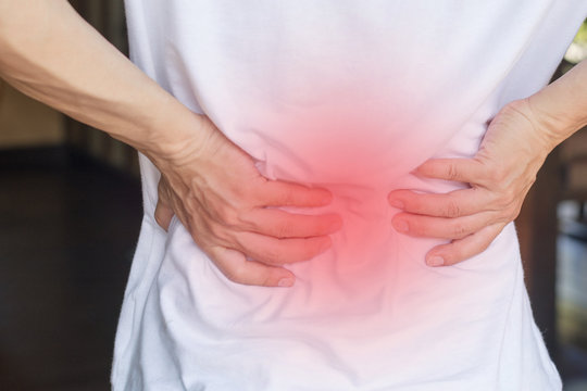Man's hands on his back with red spot as suffering on backache. Male person sick from lower back pain from Herniated or slipped discs,Degenerative, sacroiliac joint, spinal stenosis, Pancreatic Cancer