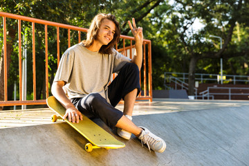 Photo of male teenager 16-18 in casual wear sitting on ramp with skateboard in skate park, during sunny summer day