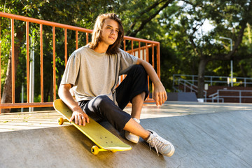 Photo of pleased skater boy 16-18 in casual wear sitting on ramp with skateboard in skate park, during sunny summer day