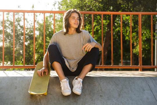 Photo of european skater boy 16-18 in casual wear sitting on ramp with skateboard in skate park, during sunny summer day