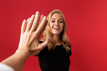 Excited woman looking camera give a high five to someone's hand isolated over red background.