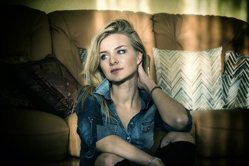Portrait of a beautiful blond woman in blue denim dress posing for camera at home, sitting