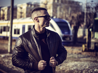 One handsome young man in urban setting in European city in front of train, standing, wearing black leather jacket