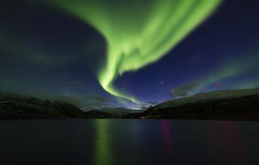 Amazing view of aurora borealis ( northern lights) over Norvegian sea .