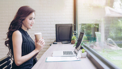 Beautiful businesswoman feel happy drinking coffee during work at the Cafe , business concept