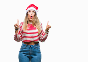 Young beautiful woman wearing christmas hat over isolated background amazed and surprised looking up and pointing with fingers and raised arms.