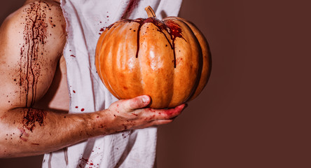 Muscular Vampire butcher man with blood. The muscular arm of a man holds an orange pumpkin. There are wounds on the arm and they are bleeding away. Halloween man with a carved Pumpkin.