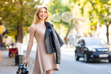 beautiful woman walks through city streets between building