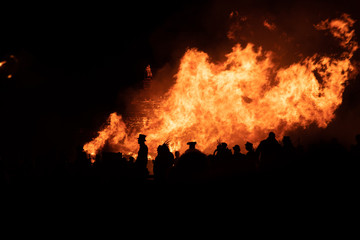 Silhouette of people in front of a bonfire