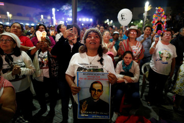 People watch the ceremony of canonization of the late Archbishop of San Salvador Oscar Arnulfo Romero at the Gerardo Barrios Square in San Salvador