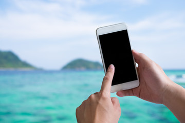 Hands using mockup smartphone with sea beach view on background.