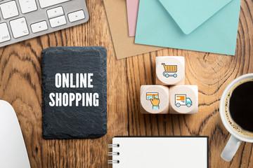 """Schiefertafel mit Aufschrift """"Online Shopping"""" und Würfel mit Einkauf-Symbolen am Computer-Arbeitsplatz"""