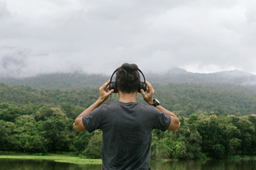 Man hands holding headphones back view. looks into the distance with nature in the horizon.Amidst the beautiful nature.
