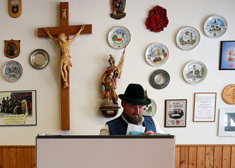 A man in traditional clothes casts his vote for the Bavarian state elections at a polling station in Maisach