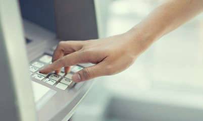 close up man hand pressing on atm machine for unlock password or counting money , business concept