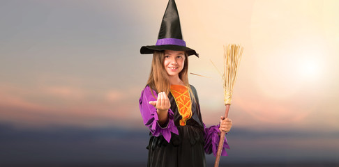 Little girl dressed as a witch for halloween holidays presenting and inviting to come at outdoor with sunset