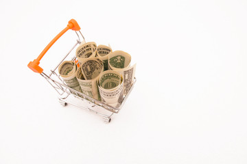 money dollars rolled into tubes in a miniature shopping cart