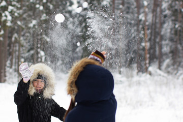 Two young girls are playing snowballs on a background of a winter forest and snow drifts