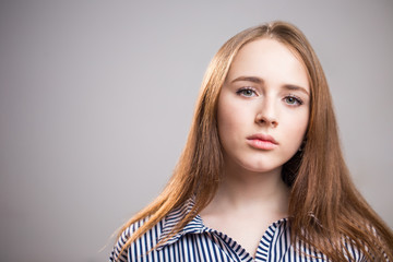 Close-up horizontal portrait of attractive student girl on grey background with copy space