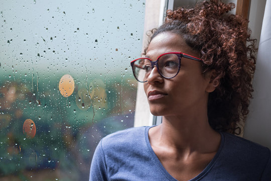 Lonely black woman near window thinking about something