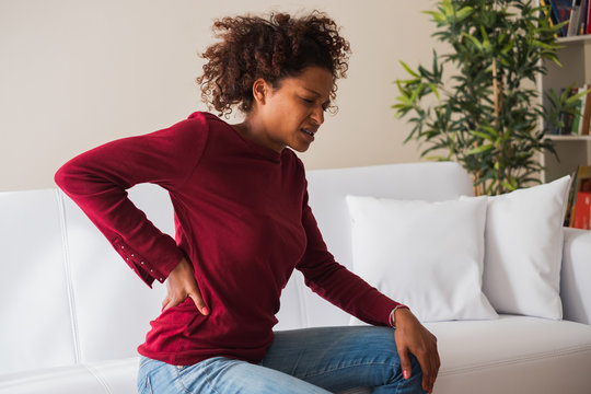 Back Neck pain. Painful woman holds with hand her lower back