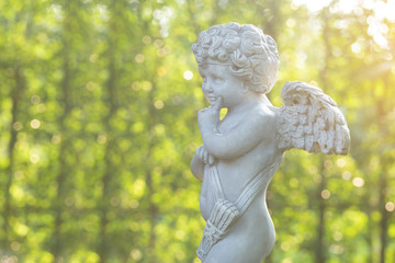 Cupid sculpture on green background in the garden