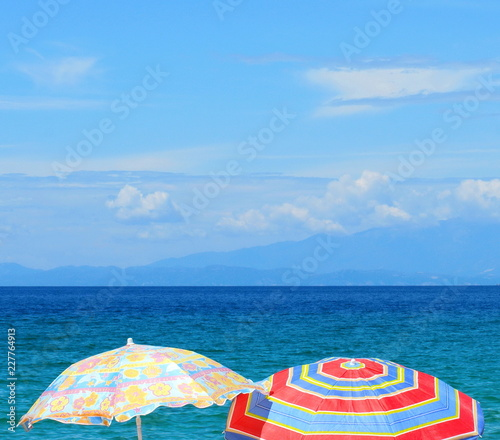 049436a17 Beach umbrella near the water. Beach umbrella on the beach. Colorful  holiday background.