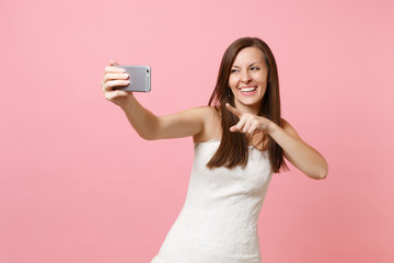 Laughing bride woman in white wedding dress pointing index finger on camera doing taking selfie shot on mobile phone, making video call isolated on pastel pink background. Wedding celebration concept.