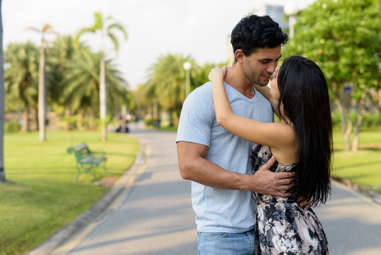 Young Hispanic couple relaxing in the park together